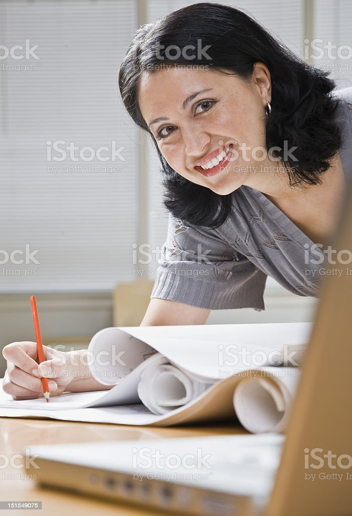 Woman Working on Blueprints royalty-free stock photo