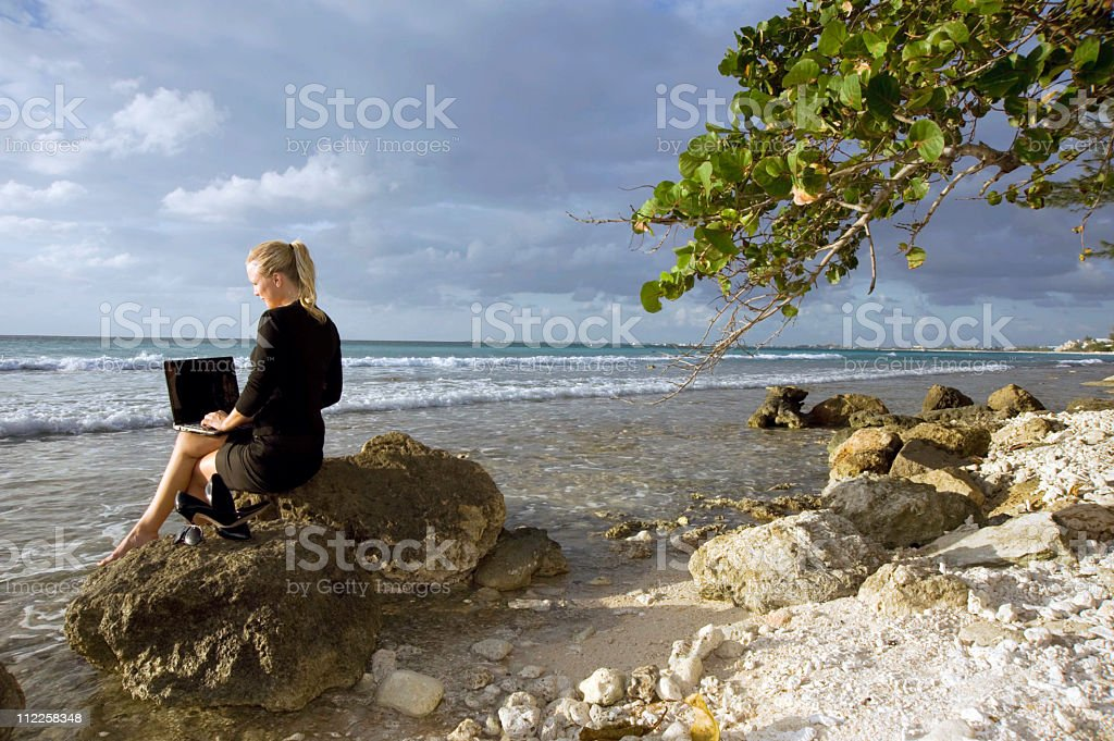 Woman working on computer at the beach 2 royalty-free stock photo