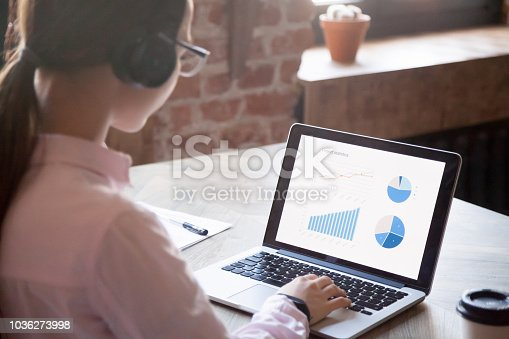 istock Woman working on computer, focus of paper on a desk 1036273998