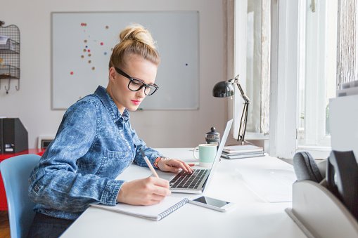 Woman Working On Computer In An Office Stock Photo - Download Image Now