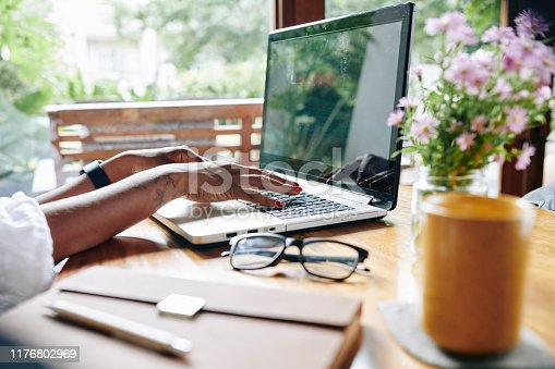 Close-up of African businesswoman sitting at the table and working on laptop at home