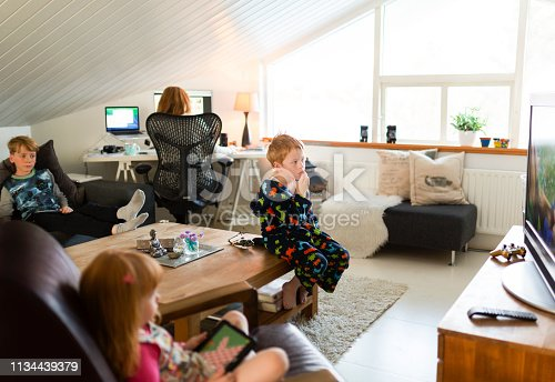 1134439364 istock photo Woman working on computer while children relaxing 1134439379