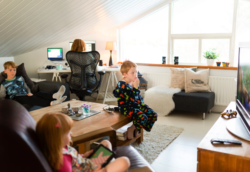Woman working on computer while children relaxing