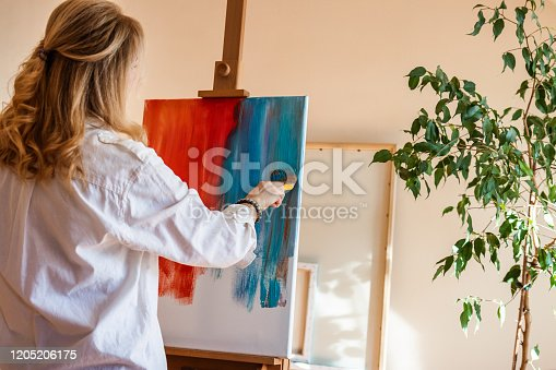 910798810 istock photo Woman working on contemporary abstract oil painting at creative studio 1205206175