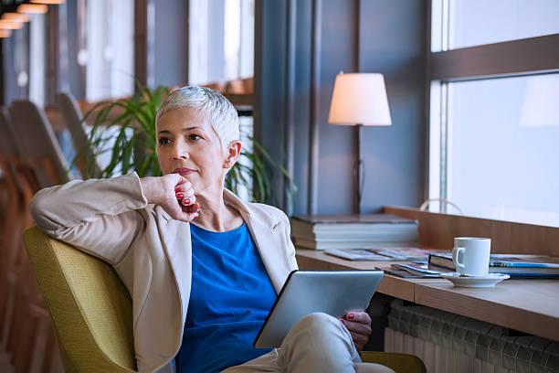 mulher a trabalhar num tablet digital no café - senior business woman tablet imagens e fotografias de stock