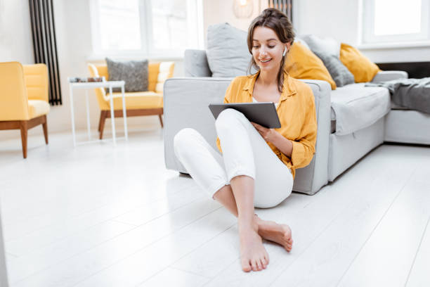 Woman working on digital tablet at home stock photo