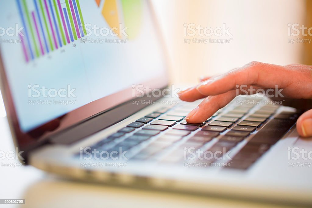 Woman working on financial data with computer stock photo