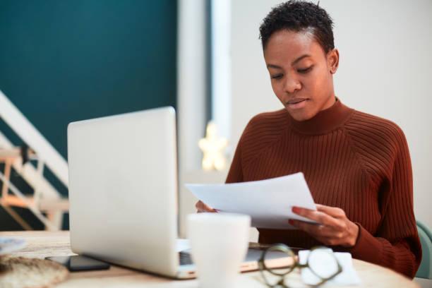 Frau arbeitet an ihren Finanzen zu Hause, füllen Steuerformulare. – Foto