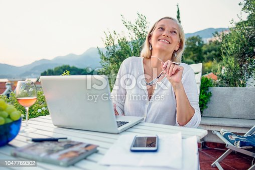 istock woman working on her laptop on the balcony 1047769302