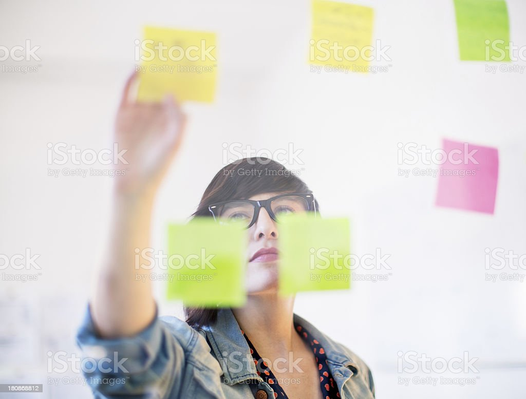 Woman working on her todos looking through glass stock photo