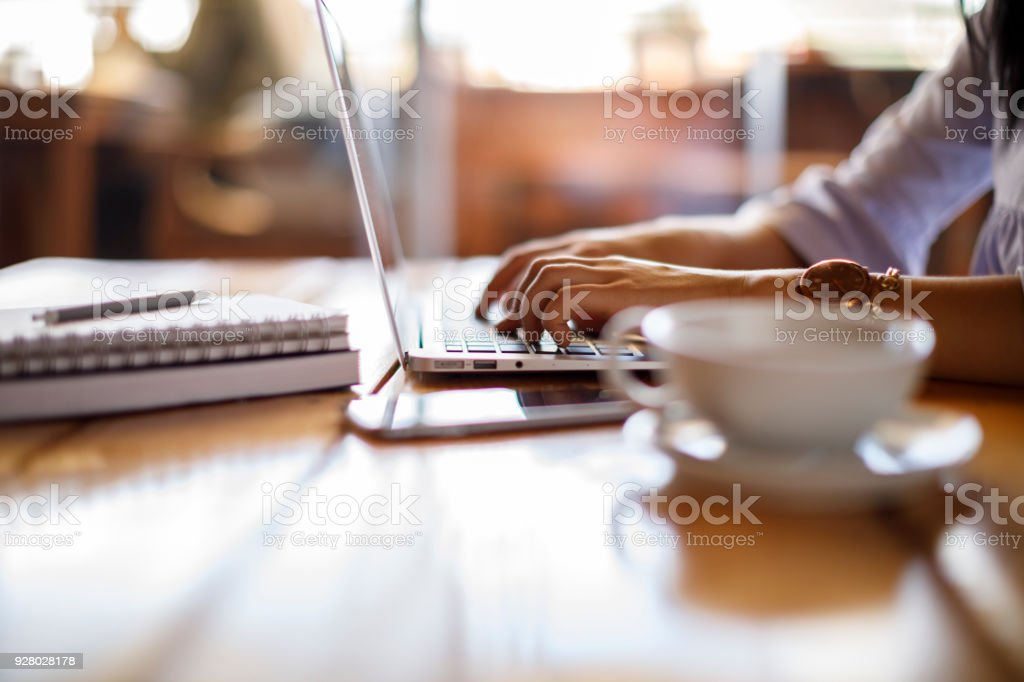 Woman working on laptop at a cafe stock photo