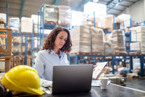 Woman working on laptop at a warehouse stock photo