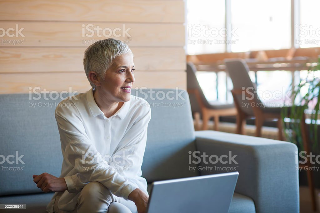 Woman working on laptop at cafe stock photo