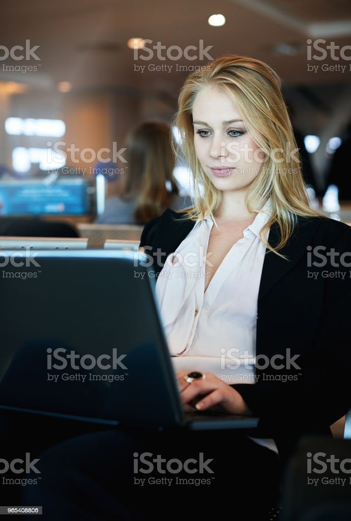 Woman working on laptop computer at airport royalty-free stock photo