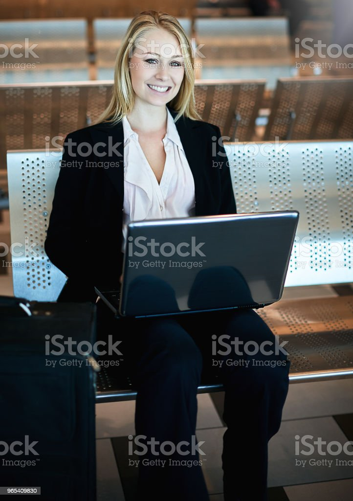 Woman working on laptop computer at airport zbiór zdjęć royalty-free