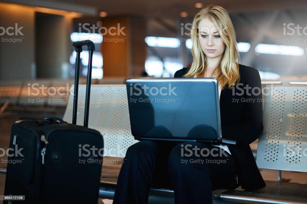 Woman working on laptop computer at airport zbiór zdjęć royalty-free