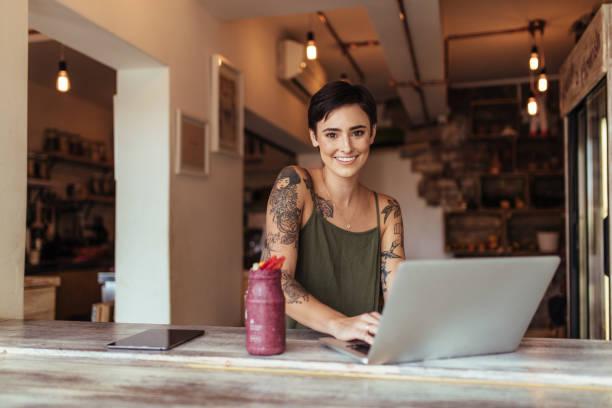 frau arbeitet auf laptop-computer - essen tattoos stock-fotos und bilder
