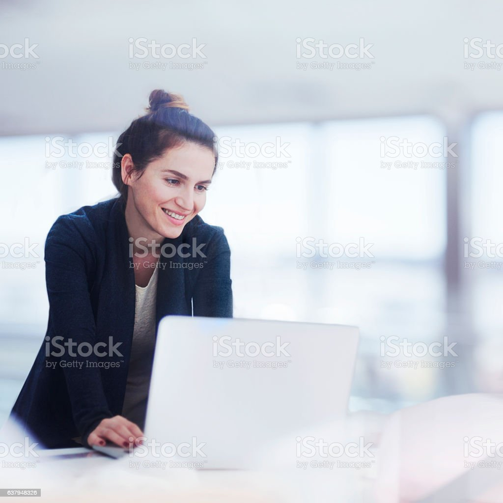 Woman working on laptop in bright office - foto de acervo