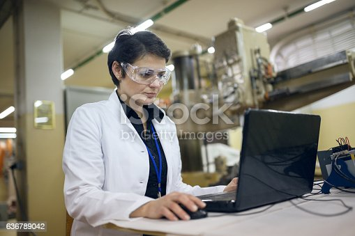 istock Woman working on laptop in production line 636789042