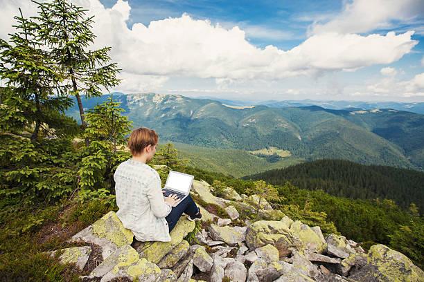 Frau arbeitet auf laptop auf dem Berg – Foto