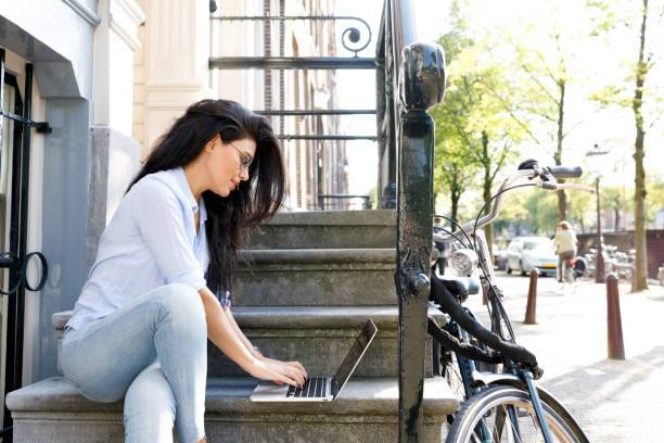Woman Working On Laptop Outdoors stock photo