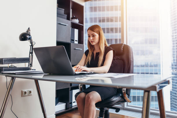 Woman working on laptop sitting at her desk in office stock photo