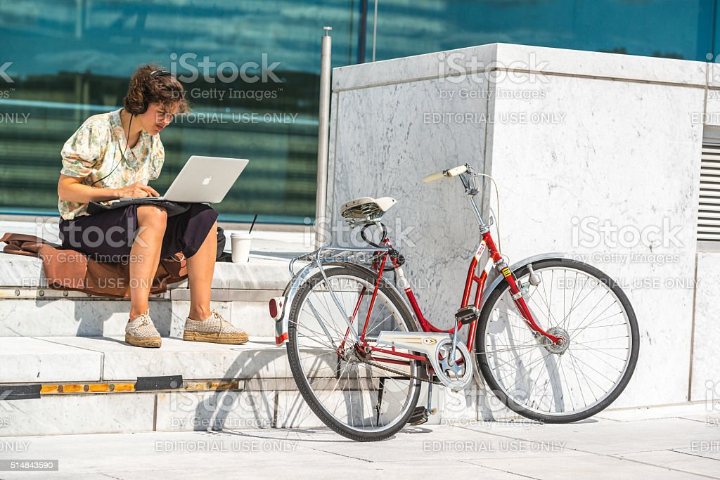 Woman working on laptop sitting near Oslo Opera House