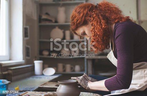 529137622 istock photo Woman working on pottery wheel 529137244