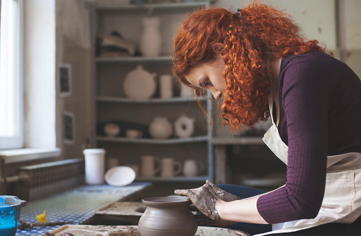 Woman working on pottery wheel