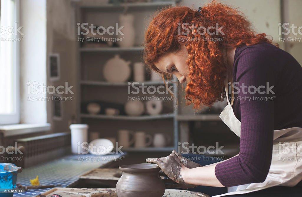 Woman working on pottery wheel stock photo
