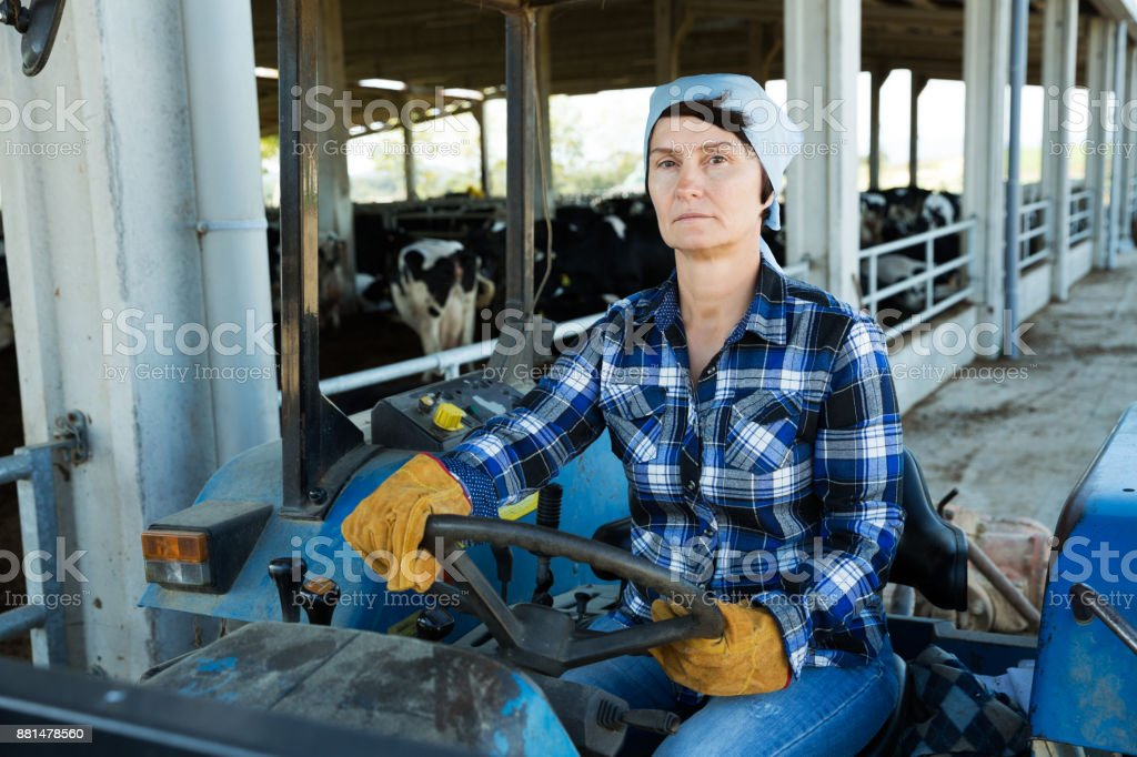 woman working on small farm tractor stock photo