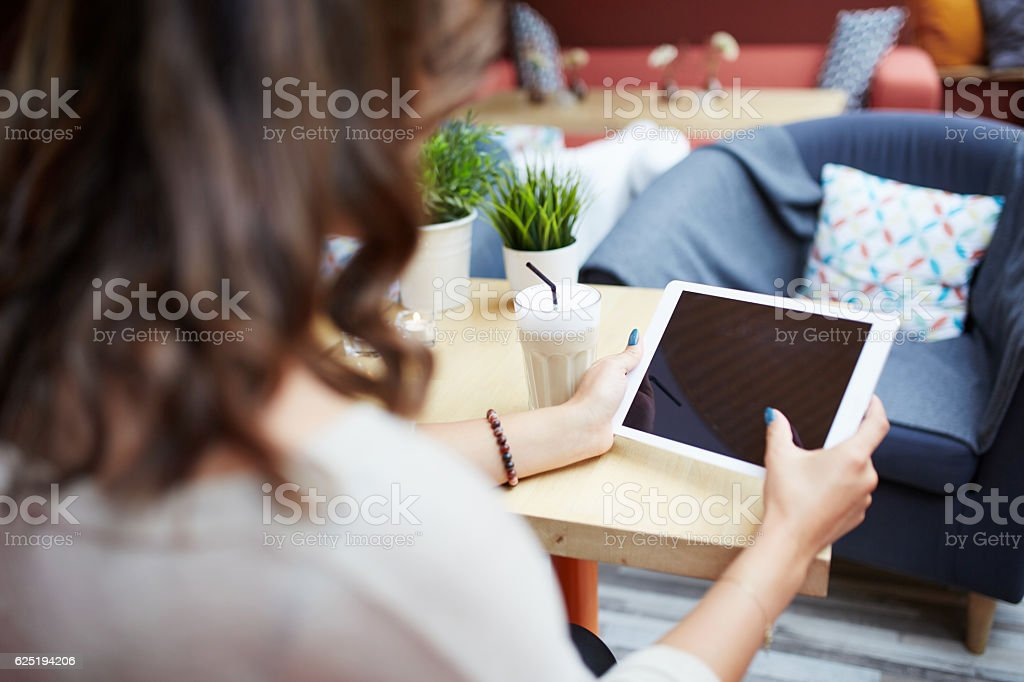 Woman working on tablet at cafe stock photo