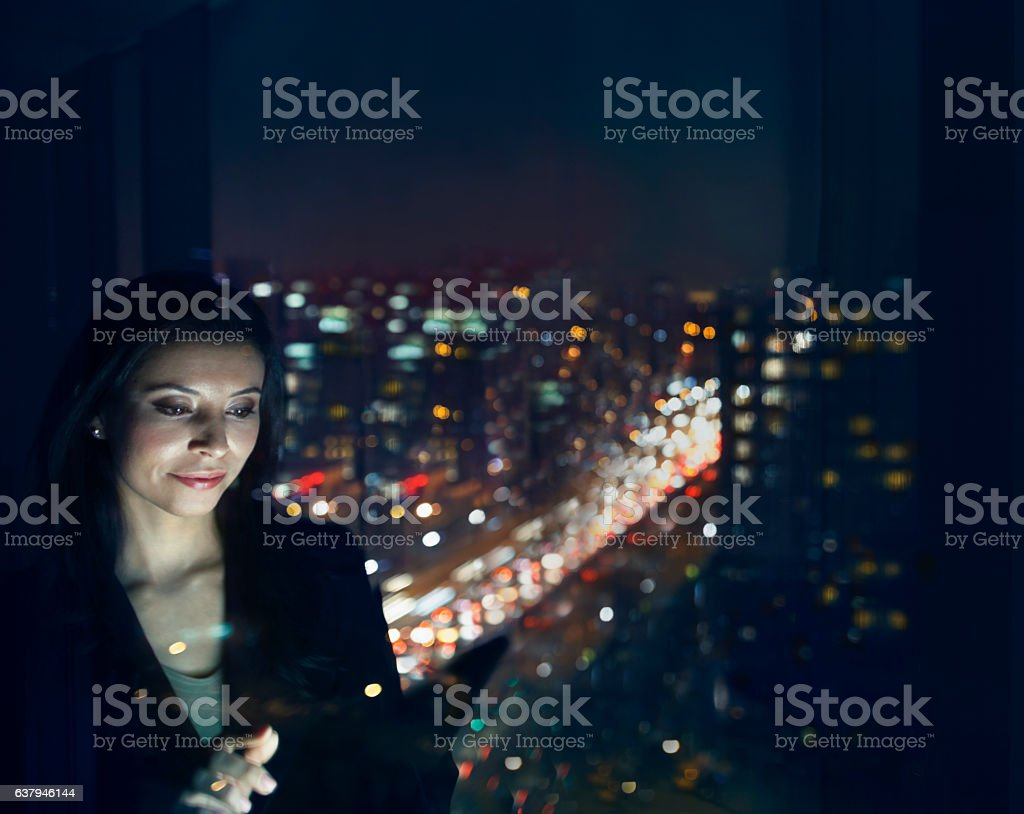 Woman working on tablet computer at night in office stock photo
