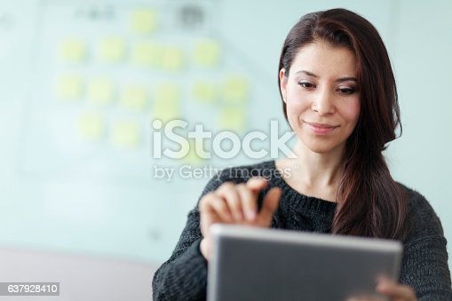 Woman working on tablet computer in studio office