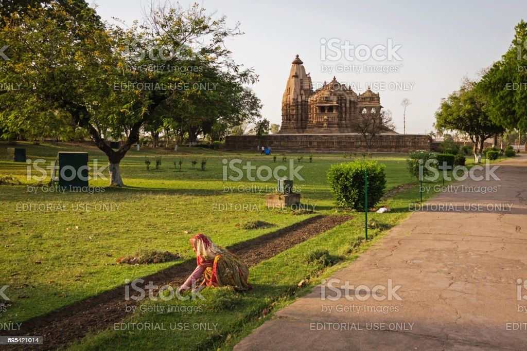 A woman working on the grass in the Western Group of Temples in the late afternoon stock photo