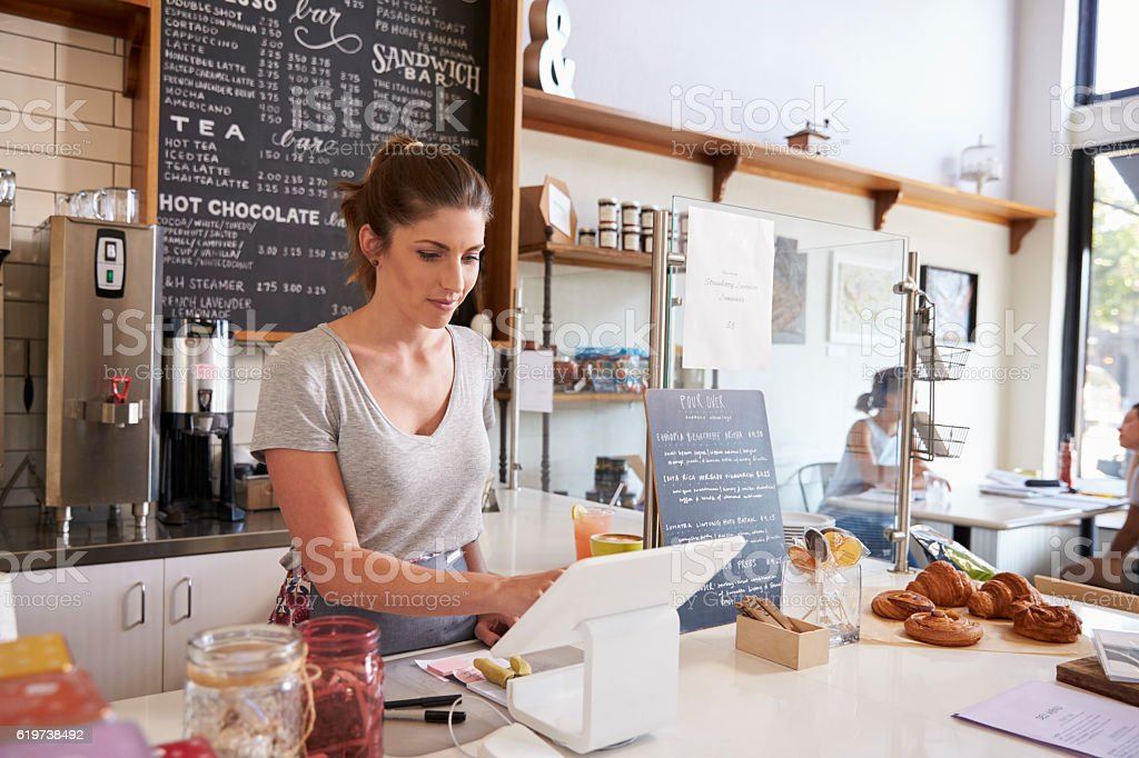 Woman working on the till at a coffee shop, wide angle stock photo