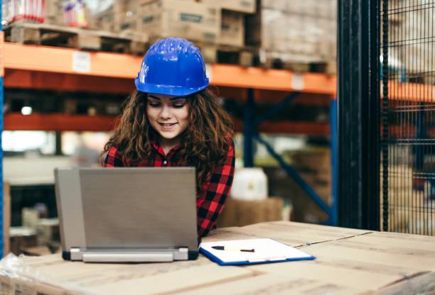 Frau auf Lager mit einem Laptop arbeitet – Foto