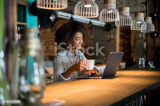 istock Woman working online at a cafe 619403886