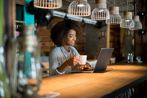woman working online at a cafe - banchi scuola foto e immagini stock