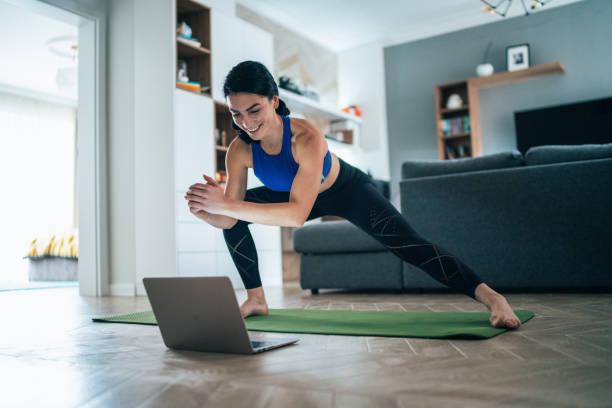vrouw die thuis uitwerkt - yoga stockfoto's en -beelden