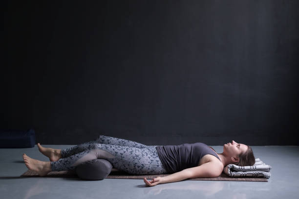 woman working out, doing yoga exercise on wooden floor, lying in Shavasana stock photo