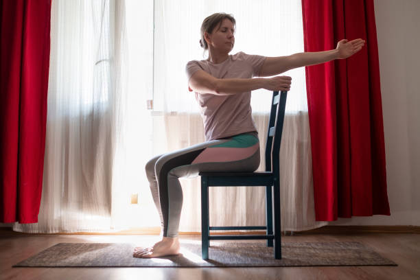 Woman working out doing yoga or pilates exercise using chair. stock photo