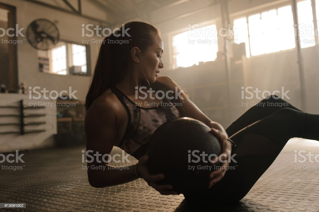 Woman working out in gym using medicine bal stock photo