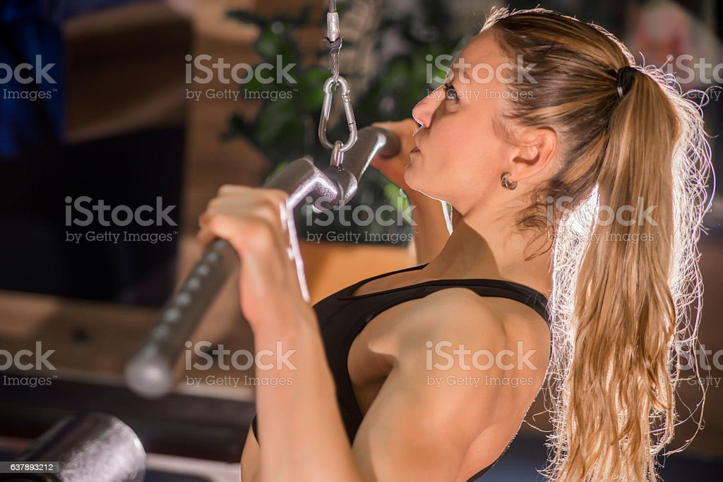 woman working out in the gym on lat machine stock photo