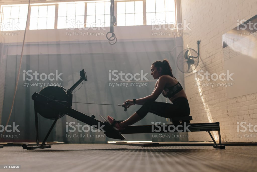 Woman working out on a rowing machine at gym stock photo