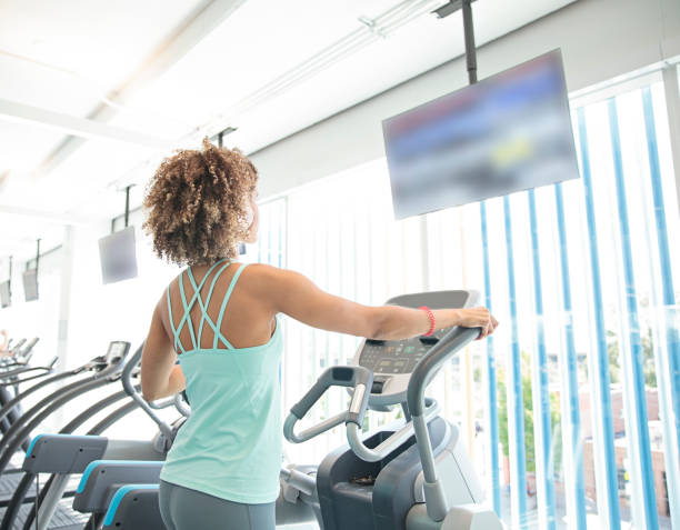 Woman Working Out on an Elliptical Machine at the Gym stock photo