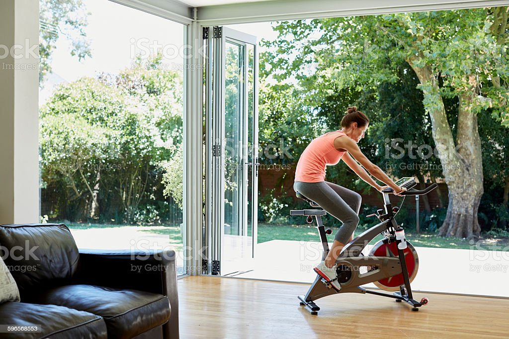 Woman working out on exercise bike at home stock photo
