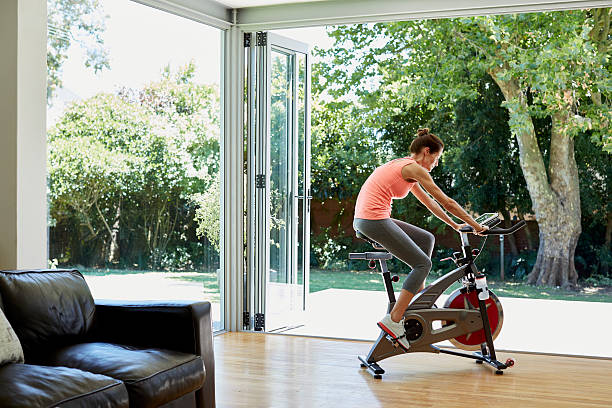 Woman working out on exercise bike at home Full length of woman working out on exercise bike at home exercise bike stock pictures, royalty-free photos & images