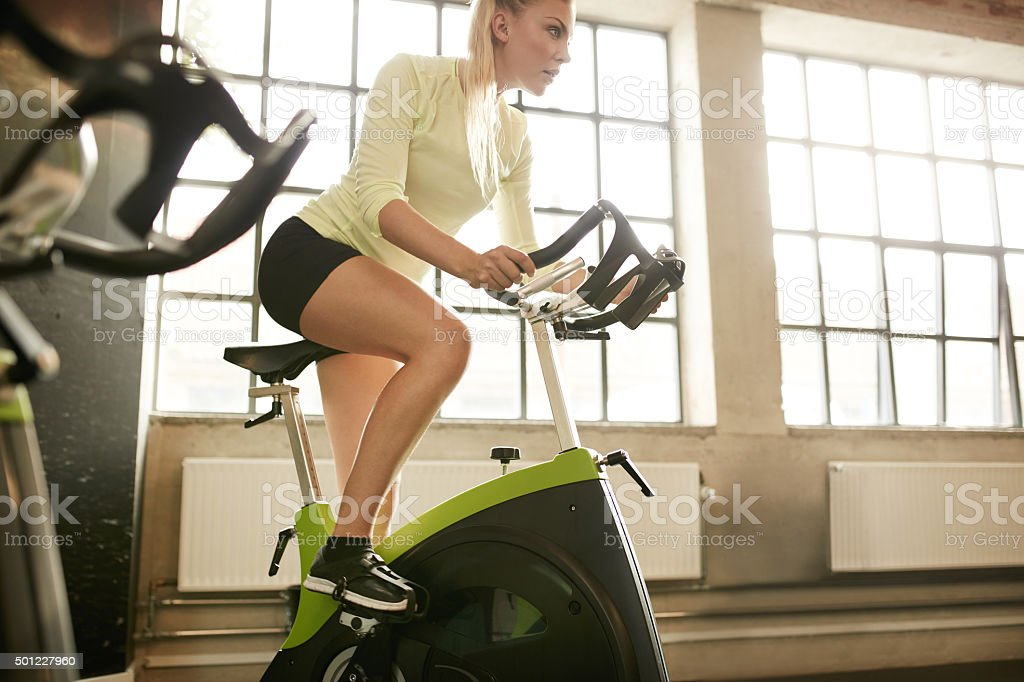 Woman working out on gym bike stock photo