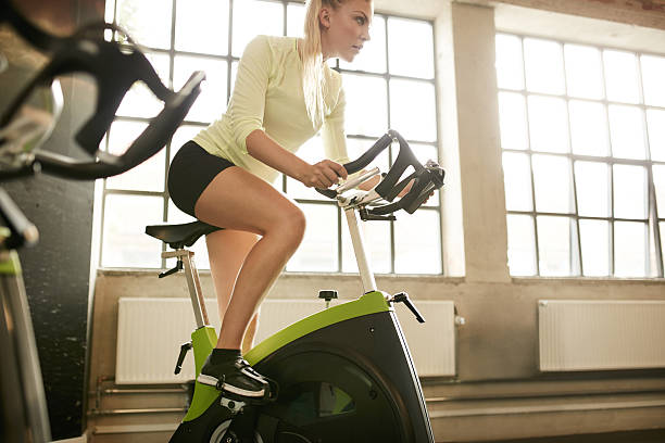 Woman working out on gym bike Fitness woman on bicycle doing exercising at gym. Fit young female working out on gym bike. exercise bike stock pictures, royalty-free photos & images
